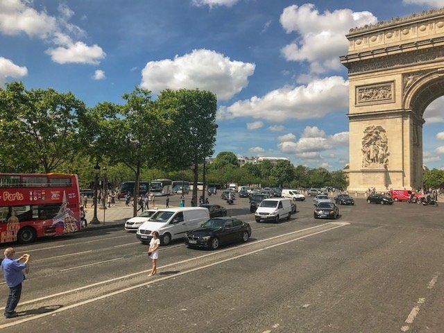 pausa para foto no meio da avenida com o Arco do Triunfo atrás